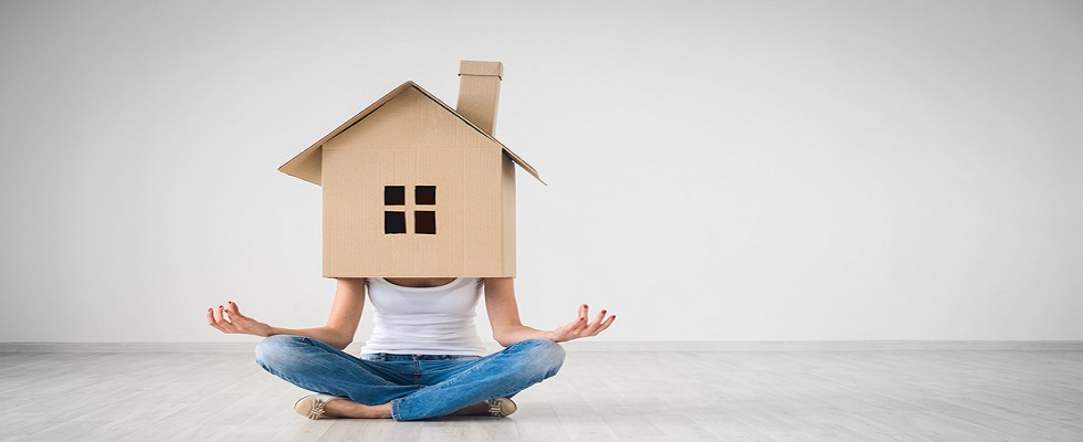 Girl in lotus pose with cardboard house on head